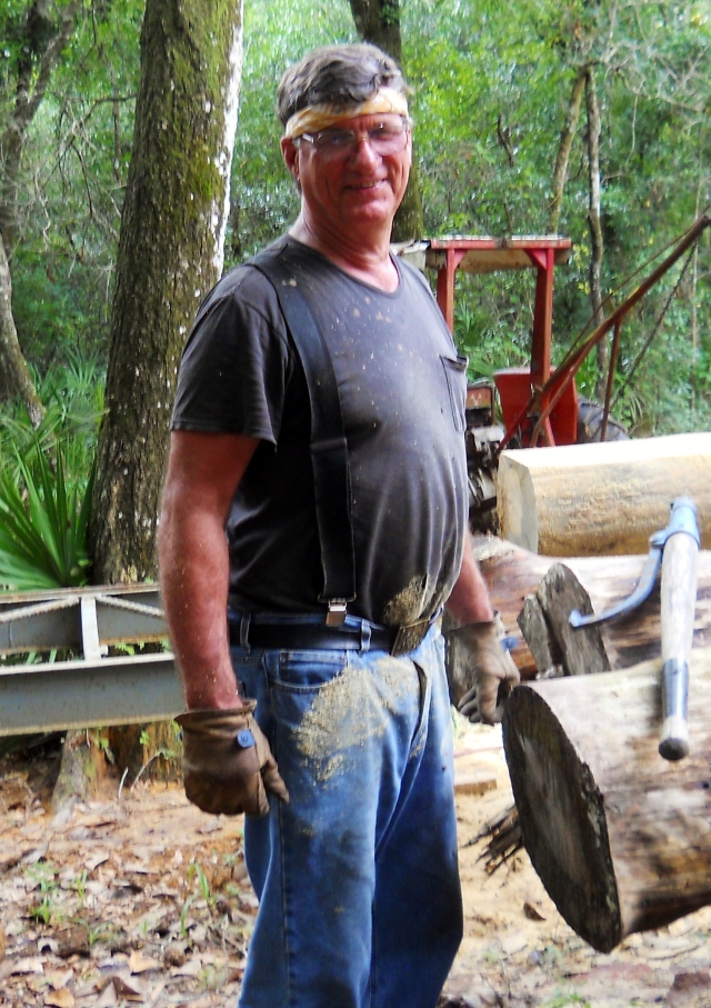 Corky, my husband, smiled without his toothpick, just to please me. He is turning those logs into boards, just for the fun of it. That orange tractor, in the background, is what he uses to maintain the access road. --- Bear